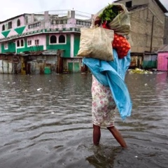 A woman wades through flood waters in a city center, with a number of possessions held in a bag on her shoulder.